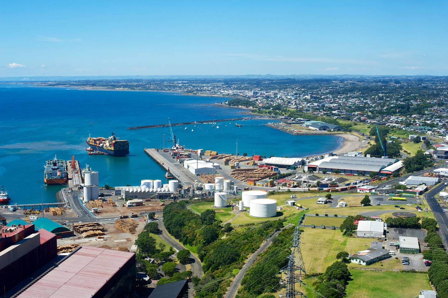 A view of the port of New Plymouth New Zealand with a container ship docking and one at the dock.