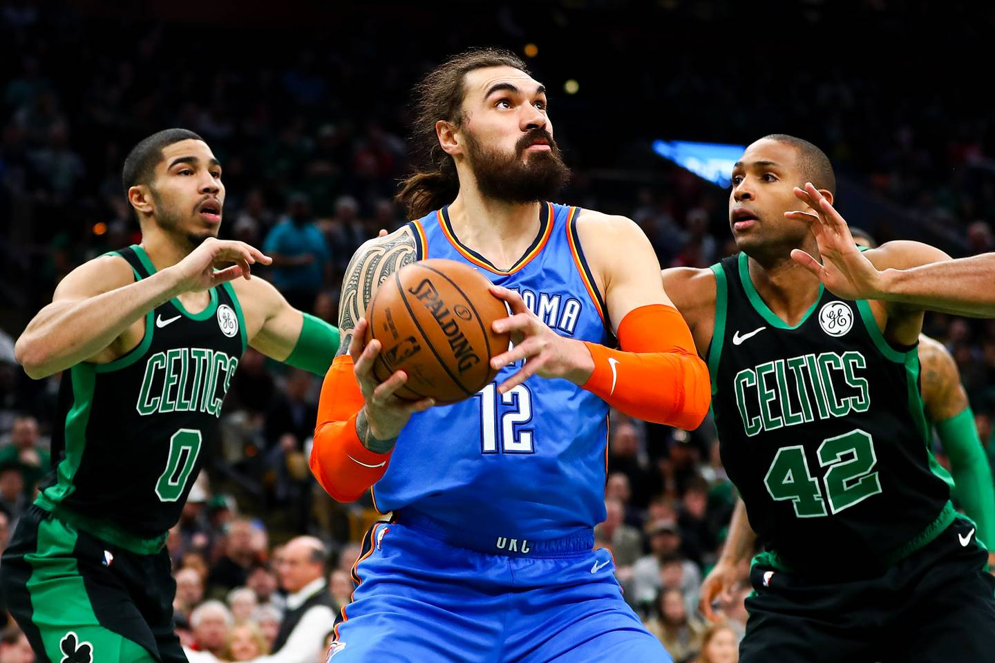 BOSTON, MA - FEBRUARY 03:  Steven Adams #12 of the Oklahoma City Thunder goes for a layup while guarded by Jayson Tatum #0 and Al Horford #42 of the Boston Celtics during a game at TD Garden on February 3, 2019 in Boston, Massachusetts. NOTE TO USER: User expressly acknowledges and agrees that, by downloading and or using this photograph, User is consenting to the terms and conditions of the Getty Images License Agreement. (Photo by Adam Glanzman/Getty Images)