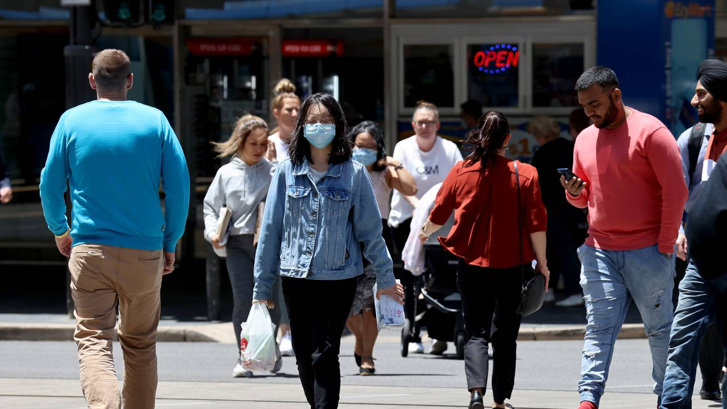 People wear protective face masks as they walk along King William Street in Adelaide, Australia.